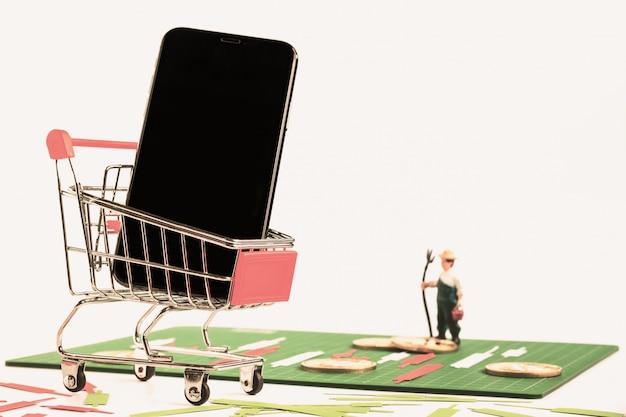 Smartphone no carrinho vermelho e framers figura modelo stand na placa verde
