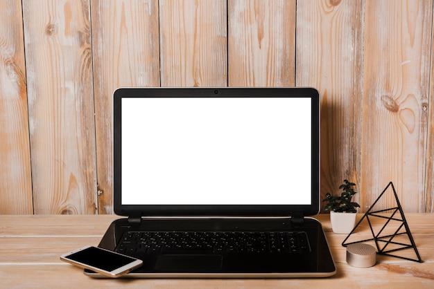 Smartphone no laptop com tela branca em branco na mesa de madeira