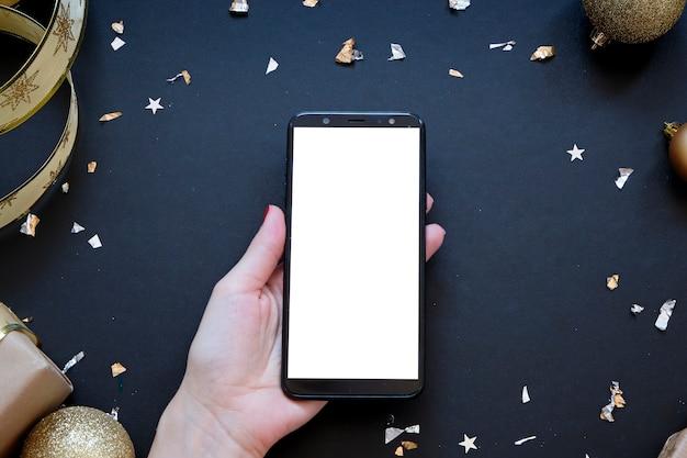 Smartphone no meio da composição de natal em preto e dourado