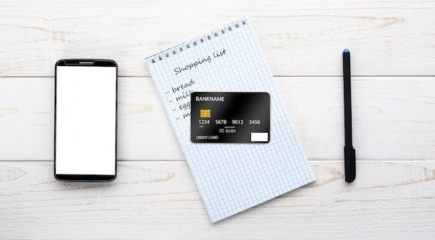 Smartphone, notebook e cartão de crédito em uma mesa branca