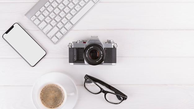 Smartphone, óculos, câmera, xícara e teclado