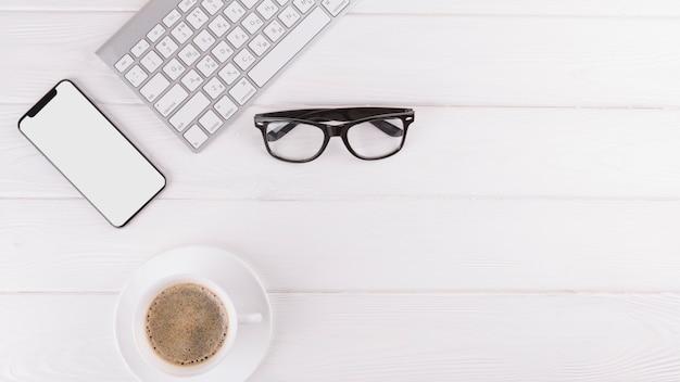 Smartphone, óculos, taça e teclado