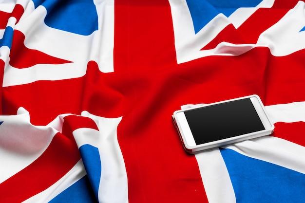 Smartphone ou telefone celular sobre a bandeira do reino unido
