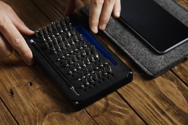 Smartphone perto da caixa do kit de ferramentas com conjunto de bits para chave de fenda em laboratório de serviço eletrônico profissional