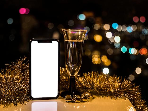 Smartphone perto de copo de bebida e ouropel