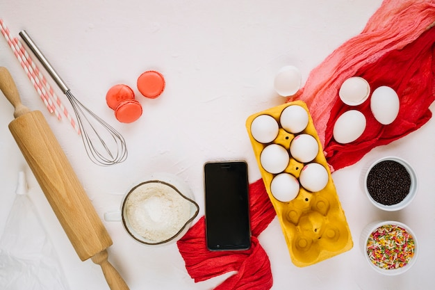 Smartphone perto de ingredientes e utensílios de cozinha