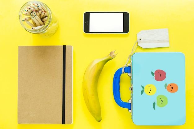 Smartphone perto de lancheira e artigos de papelaria