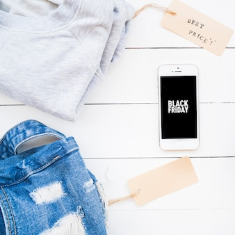 Smartphone perto de pano de brim e camisola com etiquetas