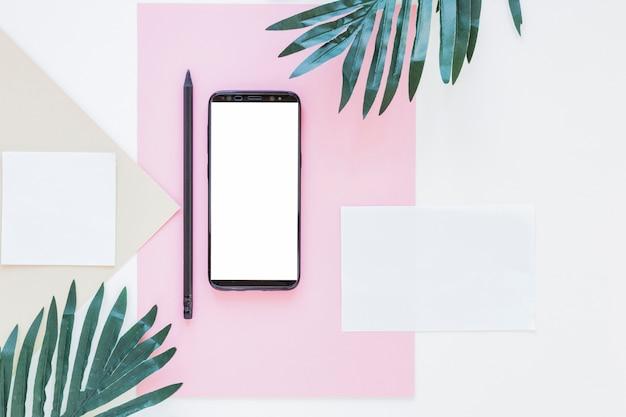 Smartphone perto de papéis e palmeiras na mesa branca