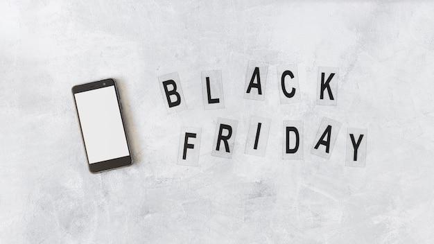 Smartphone perto de sexta-feira negra na placa cinzenta
