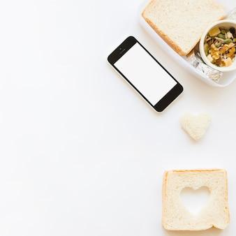 Smartphone perto de torradas e muesli