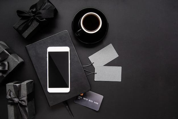 Smartphone preto, etiquetas de preços, café e presentes vista superior