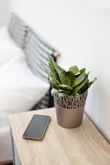 Smartphone preto na mesa de cabeceira.