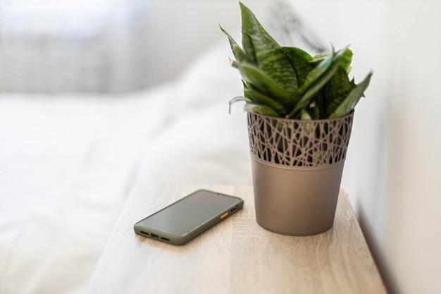 Smartphone preto na mesa de cabeceira