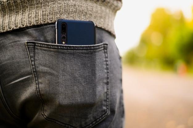 Smartphone preto no bolso de trás da calça jeans