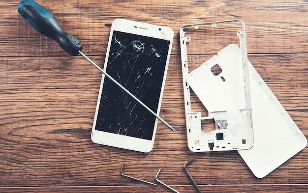 Smartphone quebrado com ferramentas na mesa de madeira