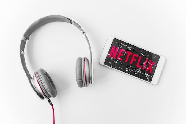 Smartphone quebrado com o logotipo da netflix perto de fones de ouvido
