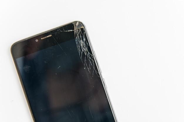 Smartphone quebrado com tela caiu no fundo branco. célula preta danificada com espaço para texto