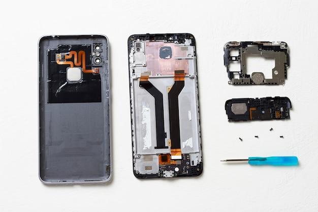 Smartphone quebrado desmontado em uma mesa branca, vista superior