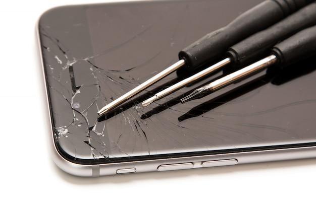 Smartphone quebrado e pequenas chaves de fenda para reparo