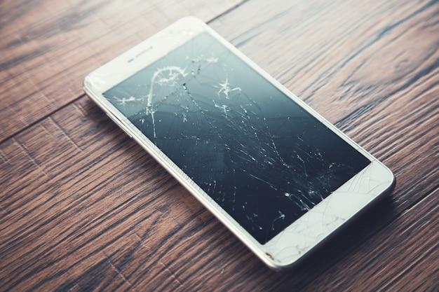Smartphone quebrado na mesa de madeira
