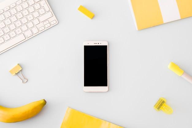 Smartphone rodeado por acessórios