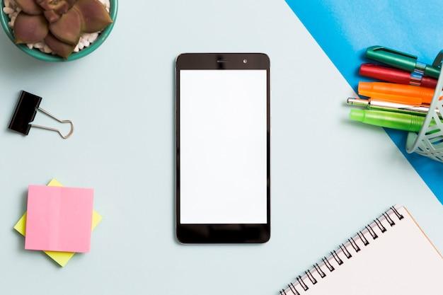 Smartphone rodeado por material de escritório