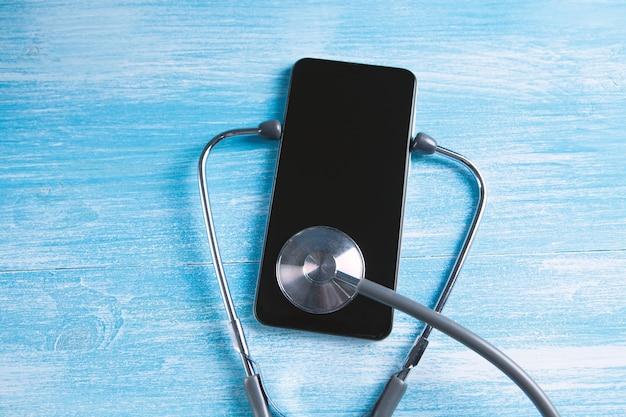 Smartphone sendo diagnosticado pelo estetoscópio - conceito de conserto e verificação do telefone