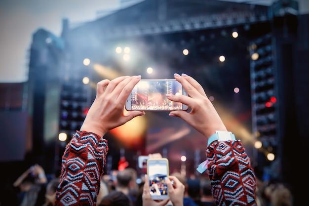 Smartphone sobre a multidão em um concerto de música. gravar show de luzes