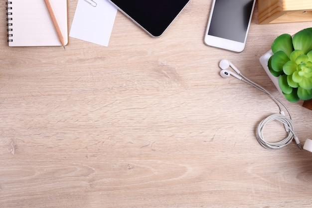 Smartphone, tablet e material de escritório em fundo de madeira