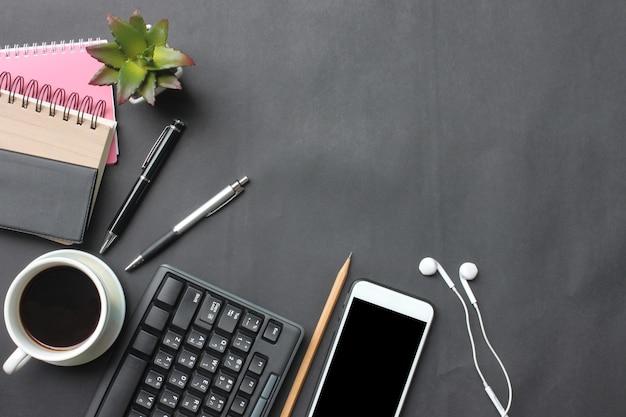 Smartphone, teclado, caderno, copo de café, pena e fontes coloca em uma mesa preta.