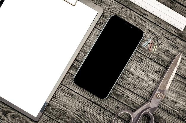 Smartphone, tesoura e prancheta na mesa