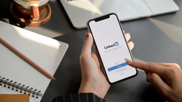 Smartphone tocando feminino com tela do linkedin. o linkedin ajuda a construir um currículo e procurar um novo emprego