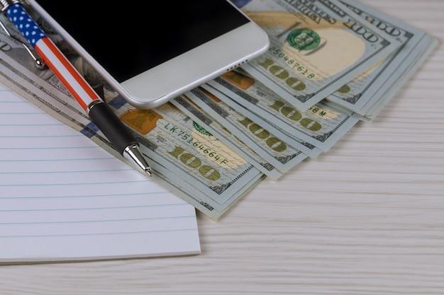 Smartphone, um caderno e uma pena em cem notas de dólar.