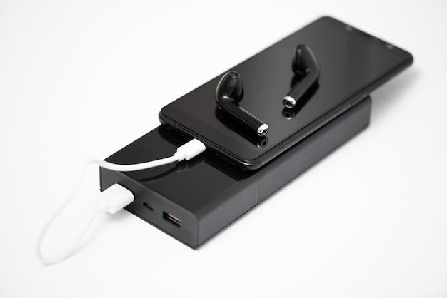 Smartphone, um fone de ouvido sem fio e um banco de energia em um fundo branco,