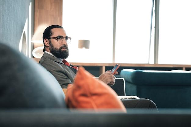 Smartphone vermelho. homem de negócios barbudo segurando seu smartphone vermelho durante uma pausa do trabalho