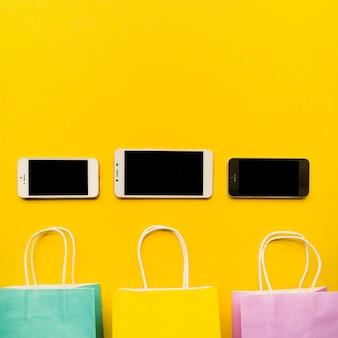 Smartphones com sacolas de compras na mesa amarela