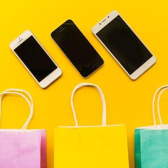 Smartphones com sacolas de compras na mesa
