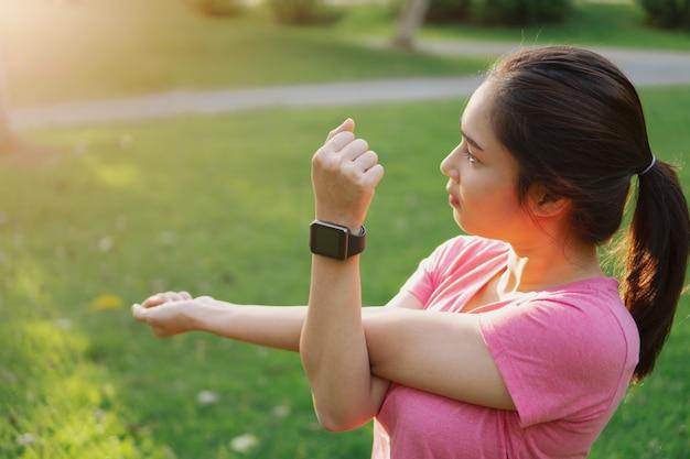 Smartwatch asiático novo do desgaste de mulher da aptidão que estica os braços, antes do exercício no parque.