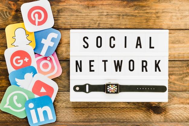 Smartwatch com ícones de redes sociais sobre a mesa de madeira