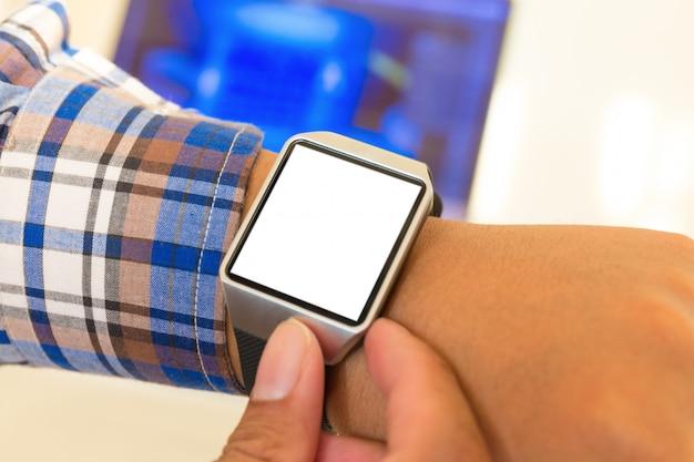 Smartwatch das mãos do homem de negócios com tela em branco.