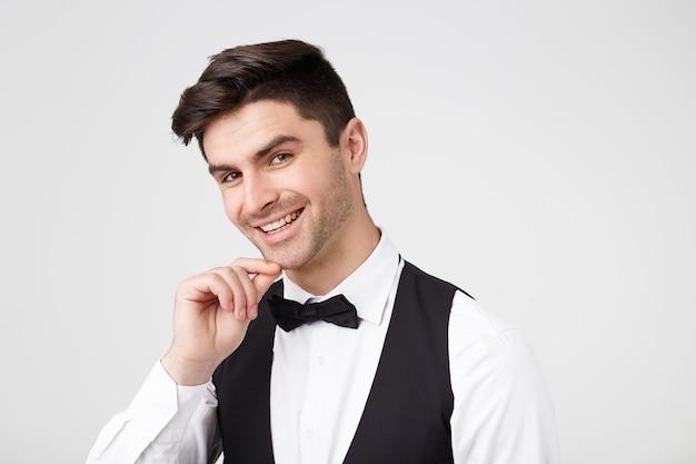 Smarty vestido com um cara atraente de cabelos escuros em uma gravata borboleta, segurando a mão perto do queixo, a cabeça ligeiramente inclinada com um sorriso encantador, sedutor e encantado