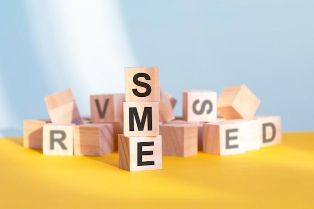 Sme escrito em cubos de madeira - dispostos em uma pirâmide vertical, fundo cinza e amarelo, sme - abreviação de pequenas e médias empresas, conceito de negócio