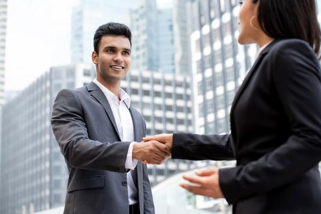Smiing bonito jovem empresário indiano fazendo aperto de mão com mulher de negócios