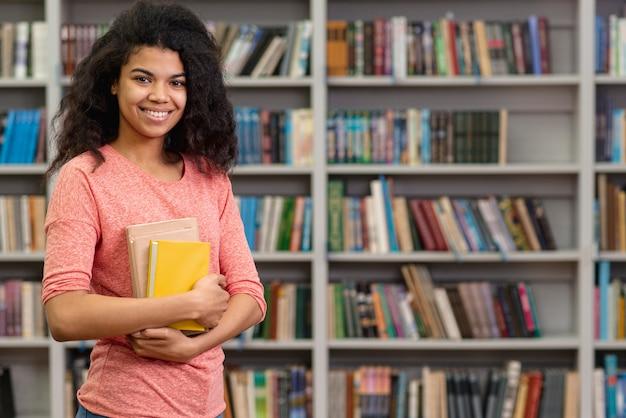 Smiley adolescente na biblioteca
