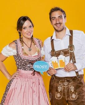 Smiley casal da baviera segurando sinais oktoberfest
