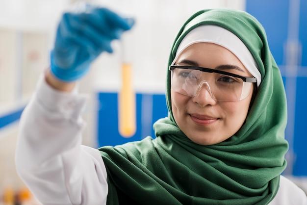 Smiley cientista feminina com hijab segurando substância