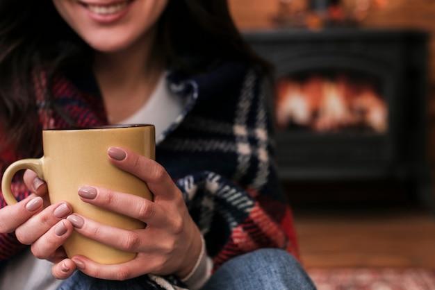 Smiley close-up mulher segurando bebida quente
