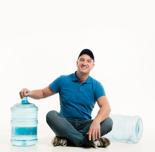 Smiley entregador posando enquanto está sentado