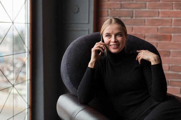 Smiley feminino no sofá falando por telefone
